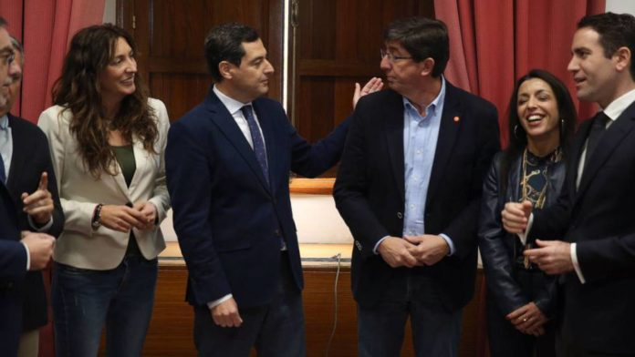 Juan Manuel Moreno y Juan Marín junto con los equipos negociadores de PP y Ciudadanos, hoy en el Parlamento andaluz.