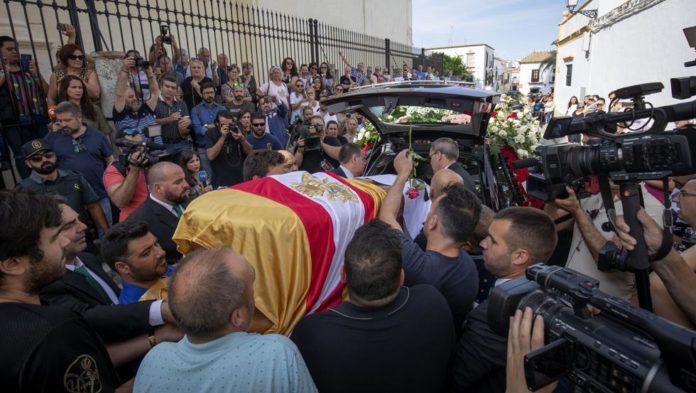 El cadáver de Reyes fue velado toda la noche en el Ayuntamiento utrerano, del que salió a las nueve de la mañana de este lunes hacia el templo cubierto con una bandera del Sevilla.