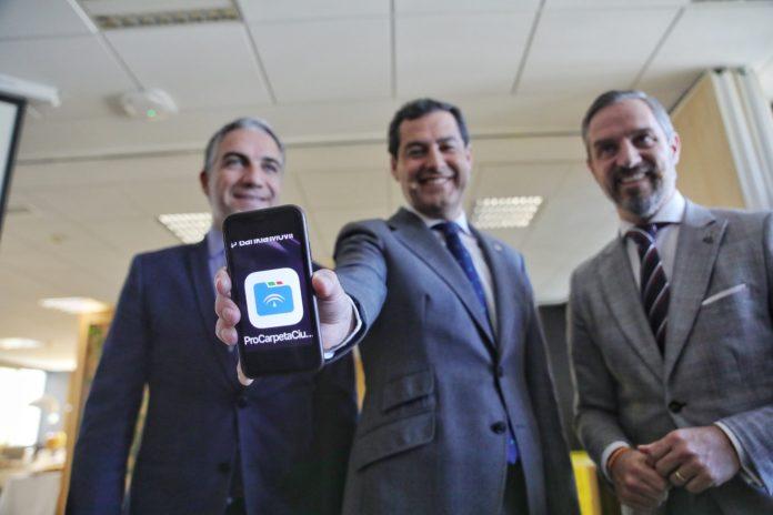 El presidente Juanma Moreno, junto a Bendodo y Bravo, con la app Carpeta Ciudadana en su móvil.